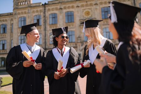 Diligent students. Group of smiling young people standing together in the campus after obtaining the Masters degree.