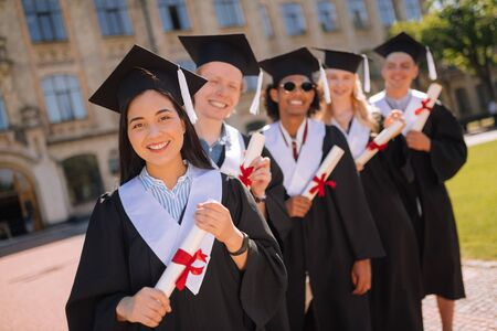 Feeling happy. Smiling graduates holding their diplomas with red ribbons on them standing one after another in the university yard. Banco de Imagens