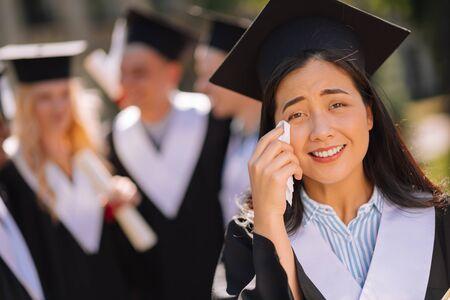 Brakująca młodość. Sentymentalna dziewczyna w czapce mistrza płacze i ociera łzy z policzków podczas ceremonii ukończenia szkoły.