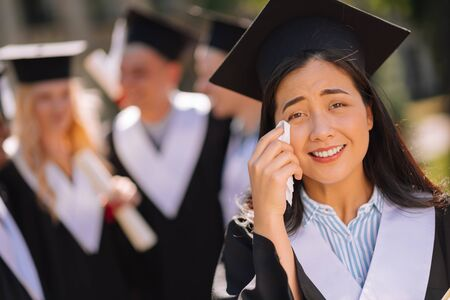 Missing youth. Sentimental girl wearing masters cap crying and wiping tears from her cheeks during her graduation ceremony. Banco de Imagens