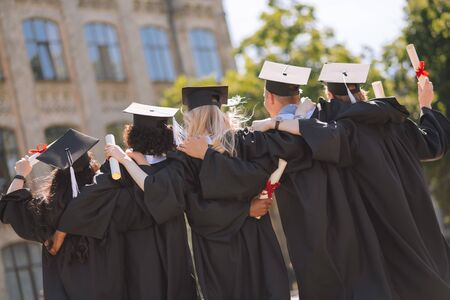 Close friends. Graduates wearing masters caps hugging each other standing side by side in the university yard. Banco de Imagens
