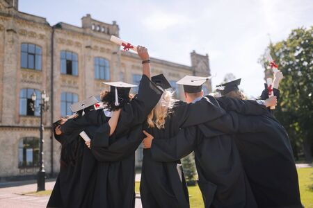 Last view. Group of graduates wearing graduation gowns and caps hugging each other in front of their university saying goodbye to it. Banco de Imagens