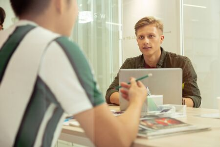 Group lessons. Concentrated blonde man sitting opposite his computer and communicating with his classmate