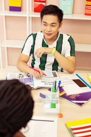 Have idea. Kind young man sitting in classroom and practicing his language Banco de Imagens