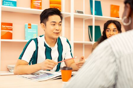 Your term. Cheerful Asian student expressing positivity while spending time in speaking club Banco de Imagens