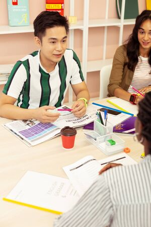 Group work. Concentrated brunette man sitting opposite his teacher while practicing his language