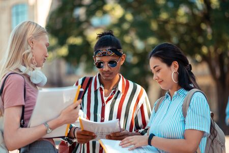 Cut-off date. Students standing together in the university yard helping each other checking their term papers. Banco de Imagens