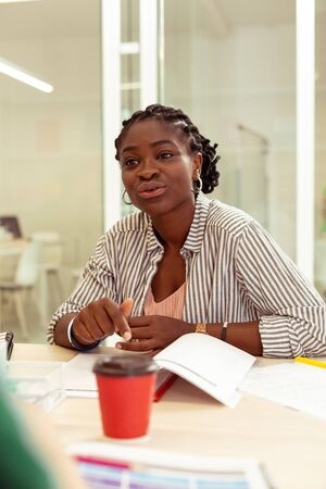 Listen to me. Cute brunette teacher sitting opposite her students while practicing speaking skills