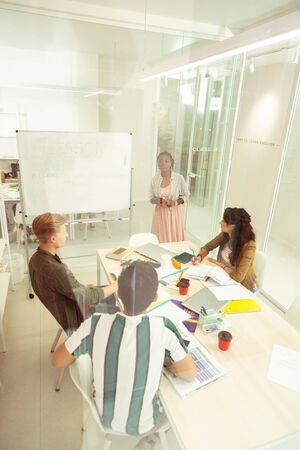 Collective discussion. Attentive blonde male person sitting in semi position while being in all ears during lesson Imagens