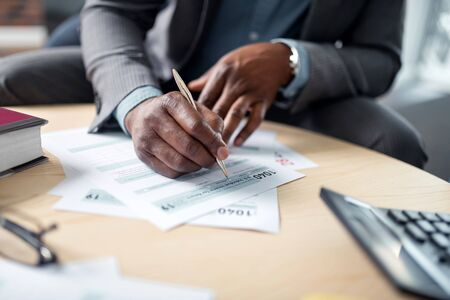 Signing documents. Close up of dark-skinned businessman holding pen and signing documents at the table