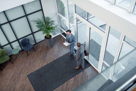 Parler avec des hommes d'affaires. Collègue à la peau foncée parlant avec des hommes d'affaires et se rendant à la réunion Banque d'images