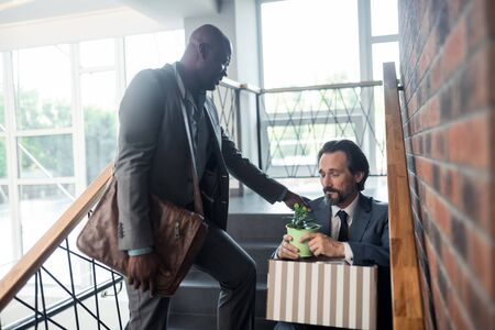 After getting redundant. Dark-skinned pleasant friend speaking with colleague after getting redundant