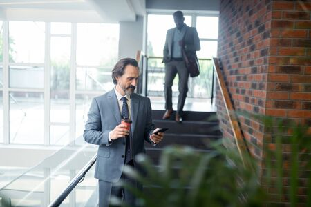 Office worker. Bearded grey-haired office worker reading message in smartphone standing near staircase Фото со стока