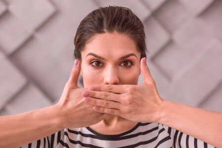 Keeping silence. The woman trying not to speak by covering her mouth with her palms