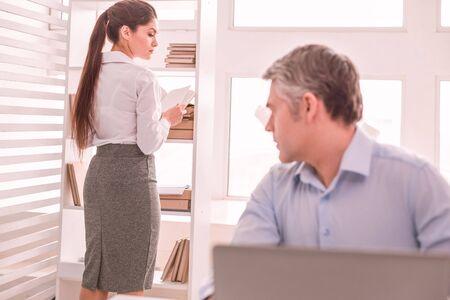 Collègue. Homme aux cheveux gris regardant sa robe de collègues féminines