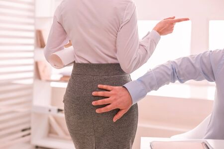 Sexual harassment. The hand touching womans backside in the office