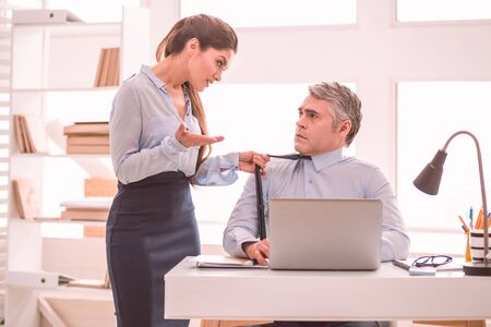 Seduction at work. A young long-haired woman trying to seduce her male colleague