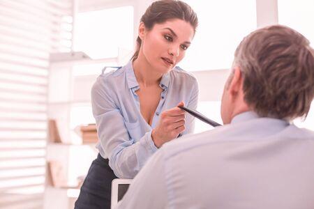 Autour du cou. Une femme a une conversation avec son patron tenant sa cravate Banque d'images