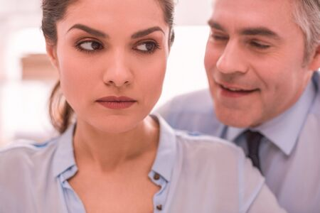 Sexism. The woman feels discriminated by her male colleague