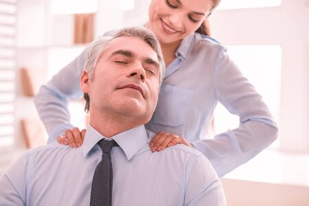 Giving a massage while working. Woman doing a message to her boss