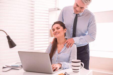 Massage sur le lieu de travail. Un homme donnant un massage à son collègue travaillant sur l'ordinateur
