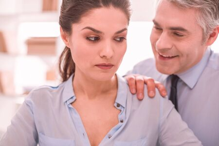 Sexist colleague. Woman feeling oppressed and discriminated by colleagues sexist jokes on her workplace