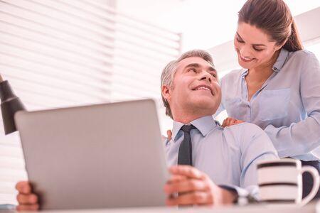 Un homme aux cheveux gris et une jeune femme ont des relations intimes sur leur lieu de travail