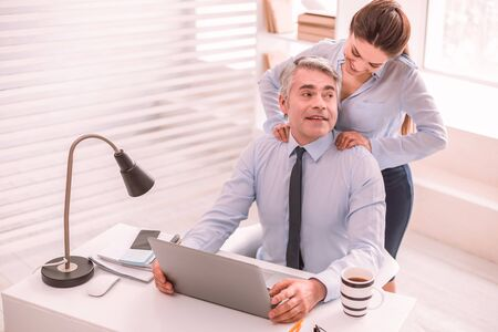 Excès de devoirs. L'assistante fait un massage à son patron Banque d'images
