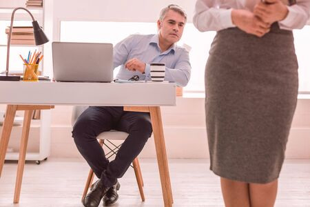 Female employee. Boss looking at his young female employee