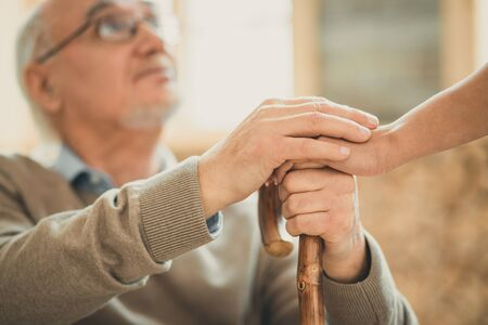Crossing their hands. Afraid old man looking on his nurse with hope while she holding his hand settling down