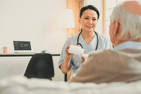 Patient during appointment. Old grey-haired man and his nurse sitting in consulting room discussing problems and health issues