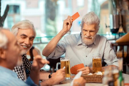 Men gambling. Grey-haired retired men gambling while drinking beer in the pub Imagens