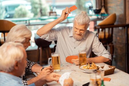 Pensioners playing cards. Grey-haired positive pensioners playing cards and drinking Imagens