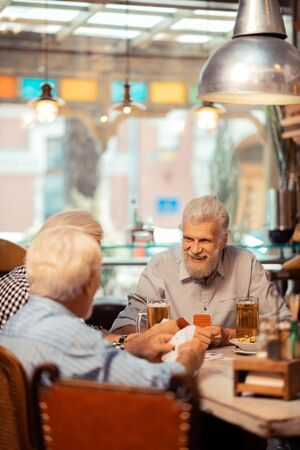 Cheerful pensioners. Cheerful grey-haired pensioners playing cards in the pub together