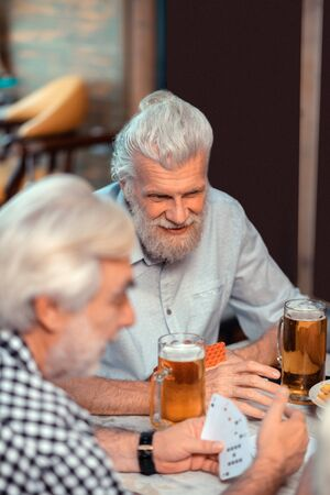 Friends drinking beer. Two old friends feeling cheerful while drinking beer and gambling