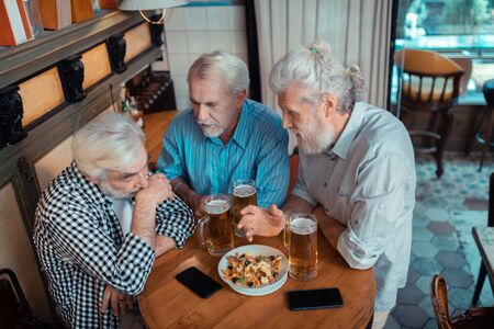 Unhappy after football. Top view of retired man feeling unhappy after watching football