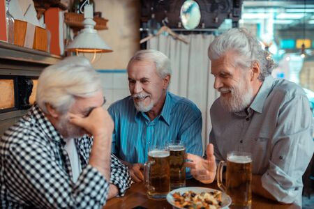 Discussing football match. Cheerful grey-haired pensioners discussing the football match in the pub