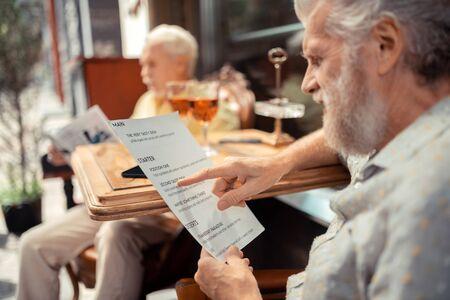 Choosing dish. Close up of grey-haired bearded man holding menu and choosing dish Imagens