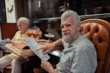 Lunch with friend. Bearded aged man choosing dish while having lunch with friend
