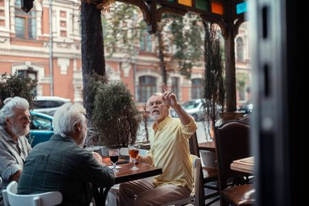 Calling for waiter. Grey-haired bearded man calling for waiter while sitting outside pub Imagens