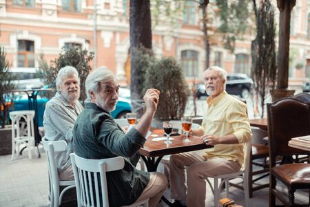 Men calling waiter. Bearded grey-haired men calling waiter while asking for receipt after drinking in pub