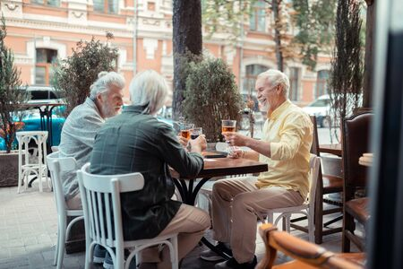 Smiling and drinking. Retired grey-haired men smiling and drinking alcohol sitting outside pub