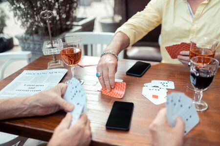Man taking cards. Man wearing bracelet and ring taking cards while gambling with old friends