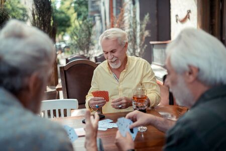 Gambling with friends. Bearded man wearing rings gambling with friends in the evening Imagens