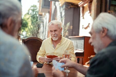 Serious aged man. Serious bearded aged man gambling with friends in the evening