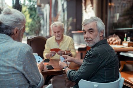 Aged men gambling. Aged retired grey-haired men gambling sitting outside the pub
