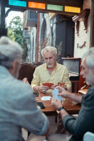 Man playing cards. Grey-haired bearded man playing cards with friends while sitting outside the pub
