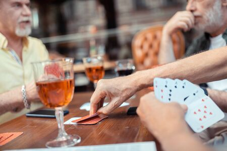 Gambling and talking. Close up of bearded grey-haired men gambling and talking Imagens