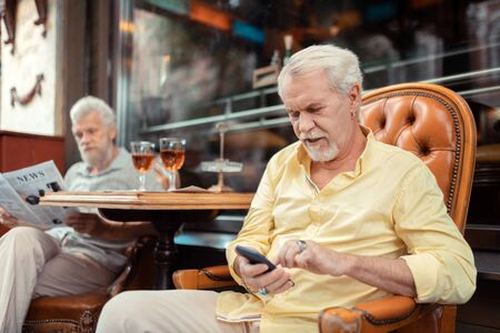 Texting wife. Aged bearded retired man wearing massive rings texting his wife while spending time with friend