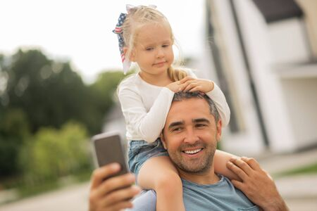 Father making selfie. Cute blonde-haired girl looking into camera while father making selfie Stock fotó